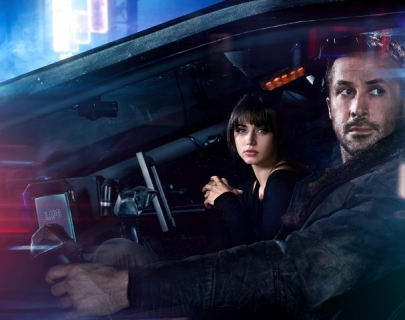 A man and a woman sat in a car surrounded by neon lights