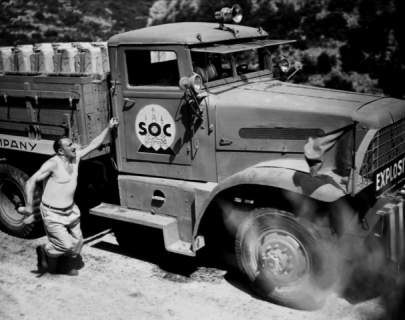 A black and white picture of a man running after a lorry