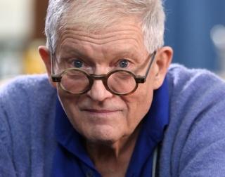 Artist David Hockney wearing glasses and a blue jumper