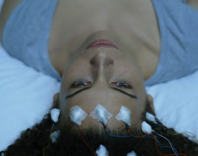 A woman lies on a bed with her curly hair fanned out behind her, and electrodes attached to her forehead.