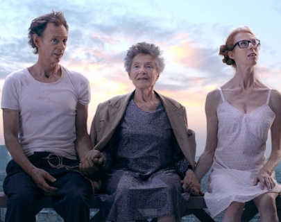 A man in a dirty white t shirt and a woman in a white dress with glasses and red hair hold hands with an elderly lady in a brown coat.