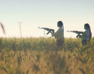 Two girls in a field holding machine guns