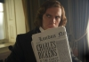 "A man in a black suit with mid-length hair holds up a London newsletter with ""Charles Dickens"" written on the front page."