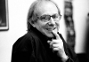 A black and white image of director Ken Loach wearing glasses and a dark coat