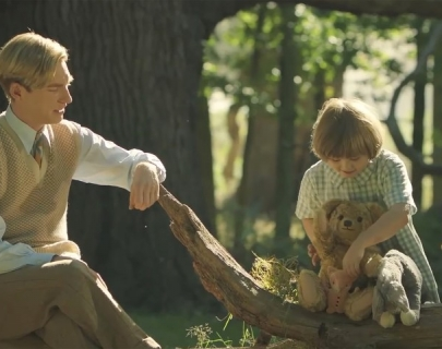 A blonde man in a shirt, tie and jumper, watches a young blonde boy play with his teddy bears on a tree branch.