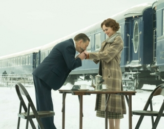 Actor Kenneth Branagh kissing actress' Daisy Ridley's hand outside in the snow with a train on the background