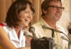 Emma Stone as Billie Jean King and Steve Carrell as Bobby Riggs smiling in front of microphones