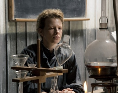 Actress Karolina Gruszka plays Marie Curie - sat behind a table full of test tubes