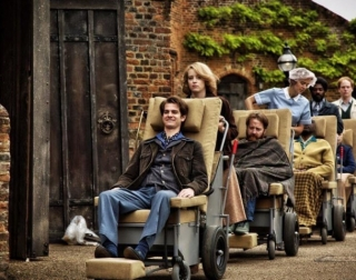 Actor Andre Garfield in Breathe being pushed in an old fashioned wheelchair at the front of a long line of patients