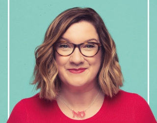 Comedian Sara Millican wearing glasses and a red jumper on a green background