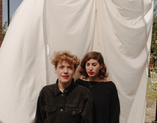 Rosa Slade and Katy Young  - aka Peggy Sue - standing in front of a white sheet looking directly at the camera