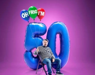 Richard Herring sitting on a chair in front of a big balloon shaped as the number 50