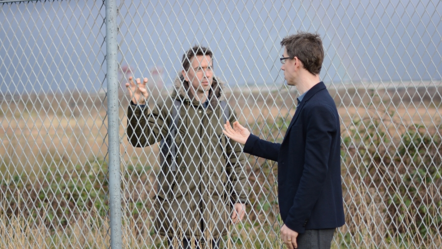 Two men - either side of a metal fence - one dressed in a suit and the other in a large green coat