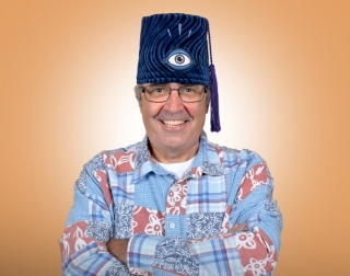 Comedian Danny Baker wearing a blue, red and white shirt and a blue fez with the image of an eye on it