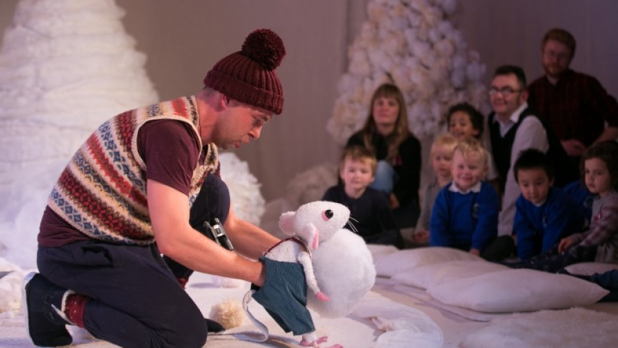 Actor holding Snow Mouse puppet in front of children