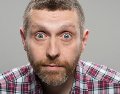 Comedian Dave Gorman staring at the camera wearing a red checked shirt