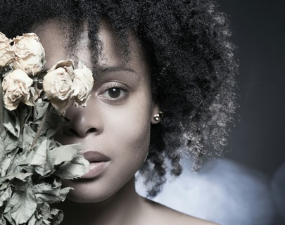 A close shot of actress Femi Keeling's face partially covered by flowers