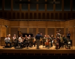 London Sinfonietta in rehearsal on a brown wooden stage