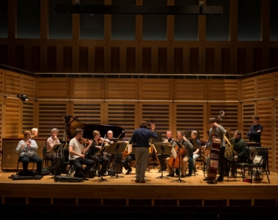 London Sinfonietta in rehearsal on a brown wooden stage