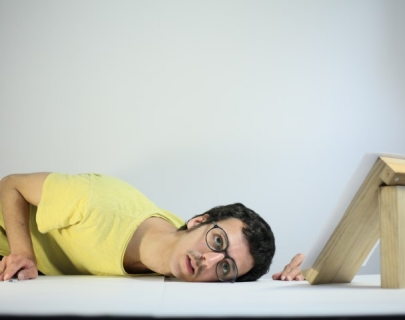 Actor wearing glasses and a yellow t-shirt resting is head on a white table as if listening