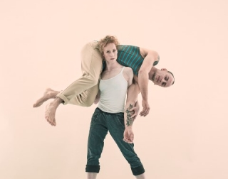 Standing woman holding a man lying on her shoulders