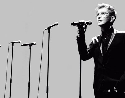Black and white picture Gareth Malone standing next to several mic stands