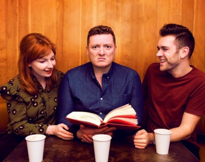 Alice Levine, Jamie Morton and James Cooper sitting at a table looking at an open book in Jamie's hands