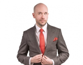 Comedian Tom Allen wearing a grey suit on a white background