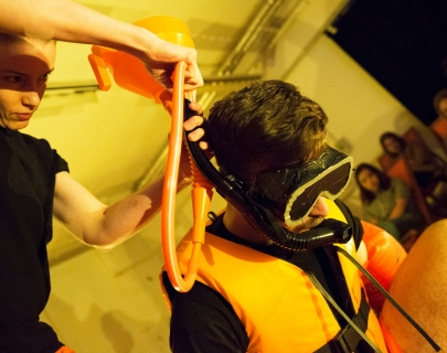 A man wearing a life vest and a scuba mask, connected to a funnel being held by another person