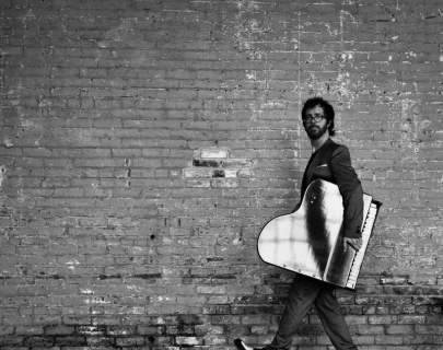 Black and white picture of Ben Folds holding a small piano and walking in front of a brick wall