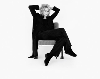 A black and white image of Joanna Lumley sitting on a chair with her hands hand behind her head