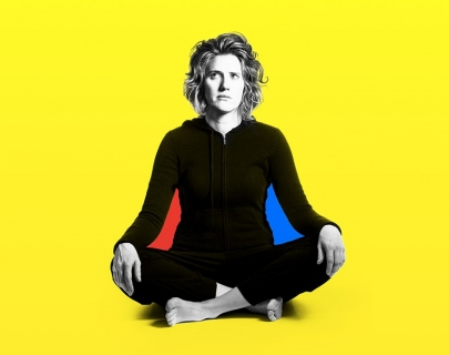 Sarah Kendall sitting with her leg crossed against a yellow background