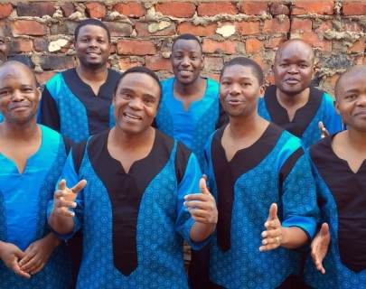 Singers wearing blue and black togas, standing in front of a brick wall
