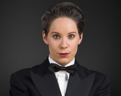 Comedian Suzi Ruffell wearing a black suit against a black background