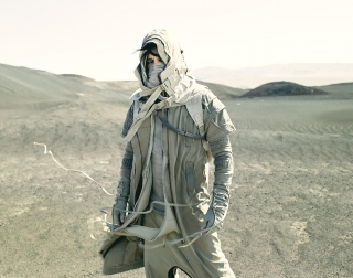 Gary Numan dressed in desert camouflage and standing in the desert