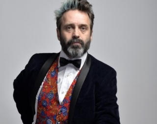 Comedian Phil Nichol wearing a suit against a white background