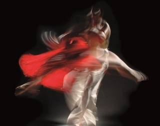 Blurry image of two dancers in white and red clothes against a black background