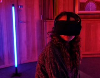 A girl sitting in a red/purple coloured room with a virtual reality headset on
