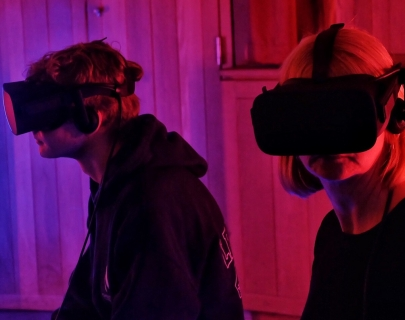 Two people sitting in a red/purple coloured room wearing virtual reality headsets