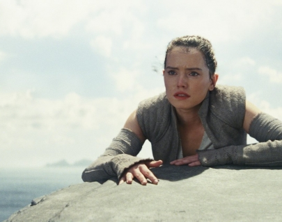 Actress Daisy Ridley as Rey resting on a rock