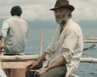 Actor Vincent Cassel in a white shirt and hat sitting in a boat