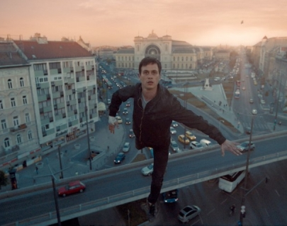 A man balancing on one leg on a tall building overlooking a city-scape
