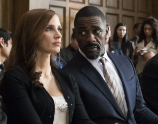 Jessica Chastain and Idris Elba in elegant clothes sitting in a courtroom