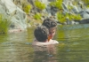 A man and woman hugging in a lake