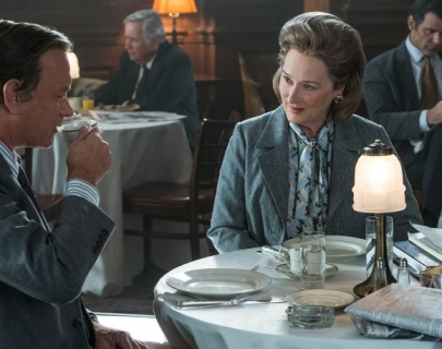 Actors Tom Hanks and Meryl Streep drinking tea sat at a table.