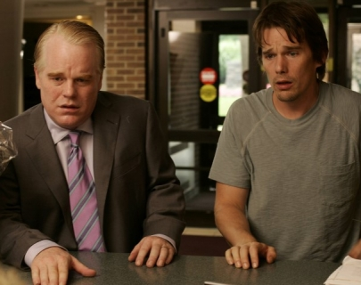 Two actors standing side by side. One in a suit and one in a t-shirt