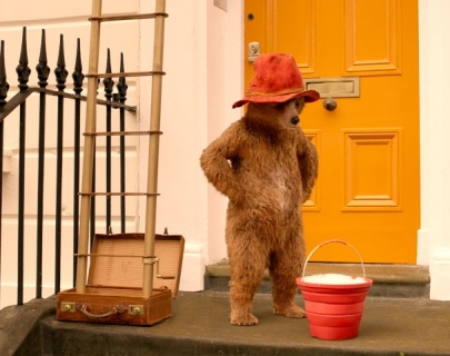 Paddington Bear wearing his signature red hat standing on a doorstep, looking at a bucket