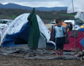 a small boy sitting outside a tent in a refugee camp