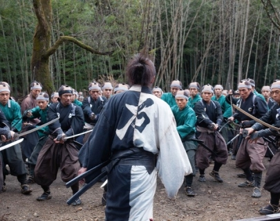 A traditionally dressed Japanese warrior faces a crowd with swords
