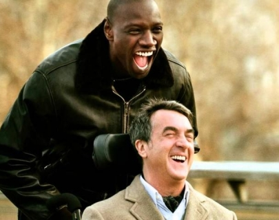 Image shows a scene from the film Untouchable of a black man pushing a white man in a wheelchair